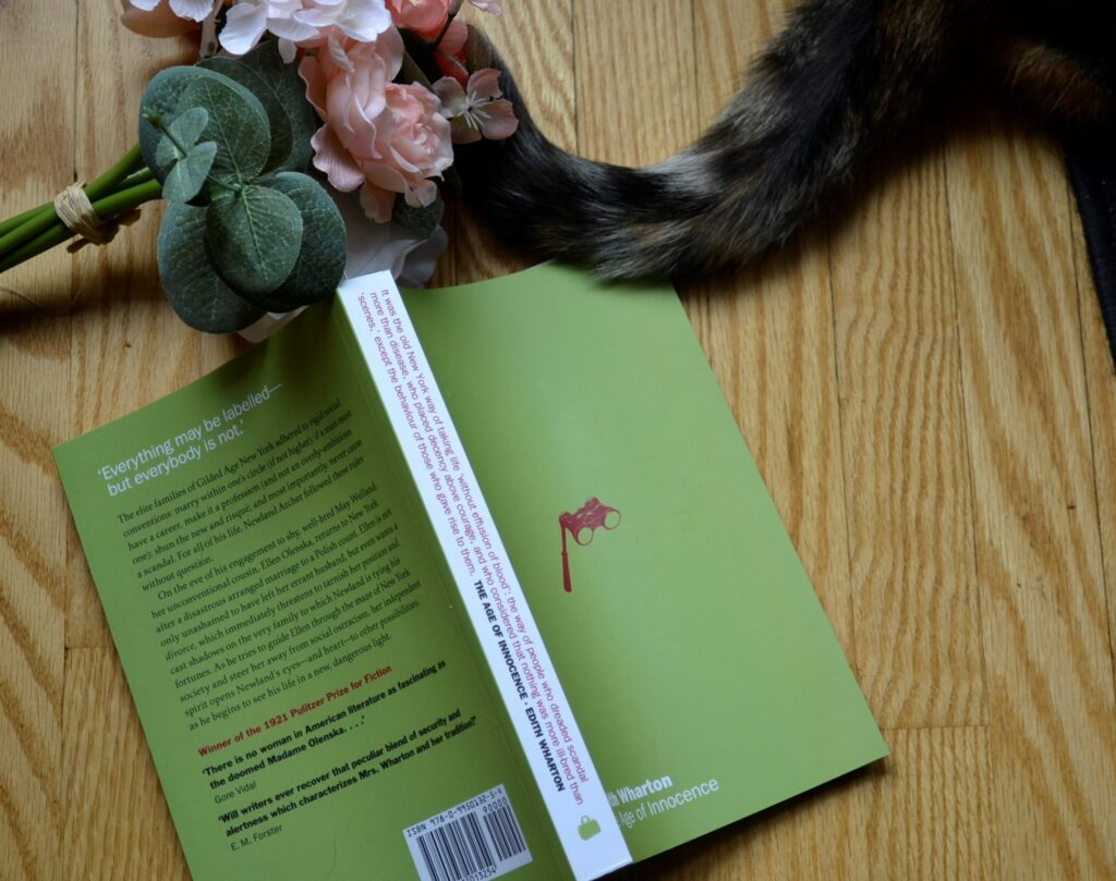 A calico cat tail and pink flowers beside a green book.