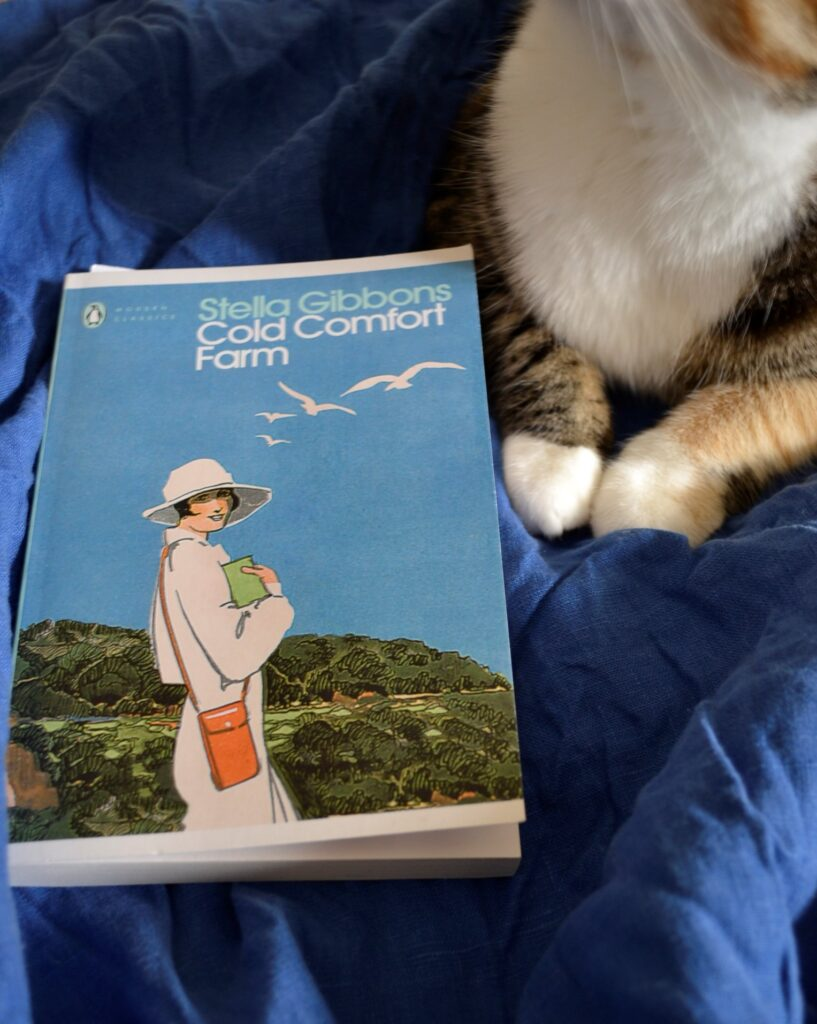A calico tabby sits bside Cold Comfort Farm.