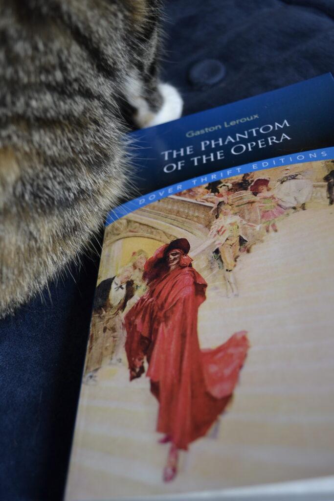 Calico paws beside The Phantom of the Opera.