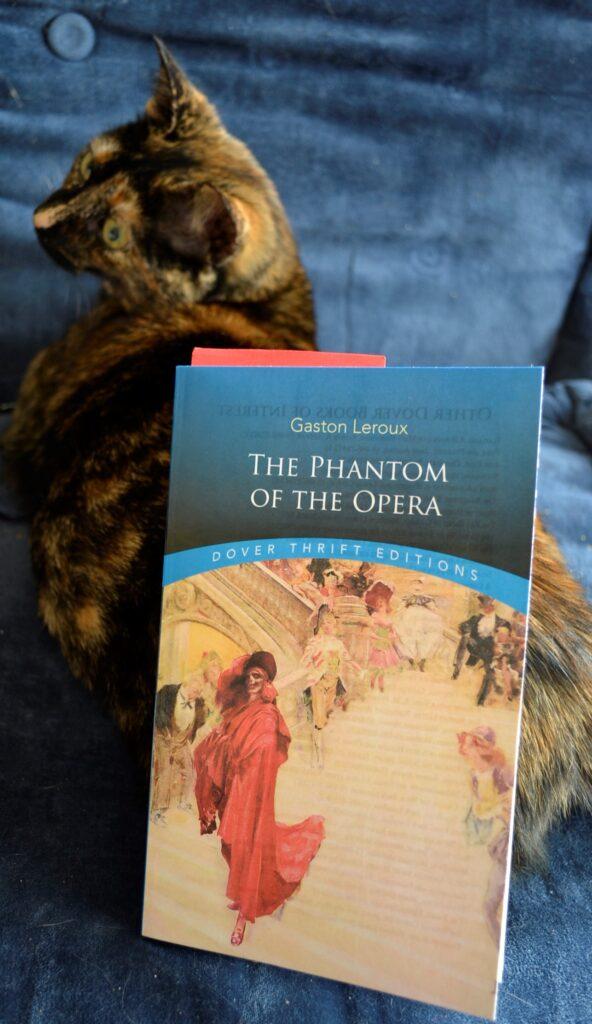 A tortoiseshell kitten sits beside The Phantom of the Opera.
