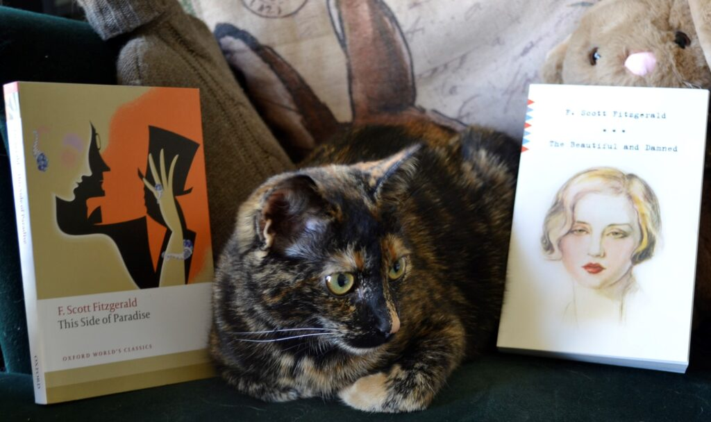 A tortoiseshell kitten sits beside two books by the Fitzgeralds.