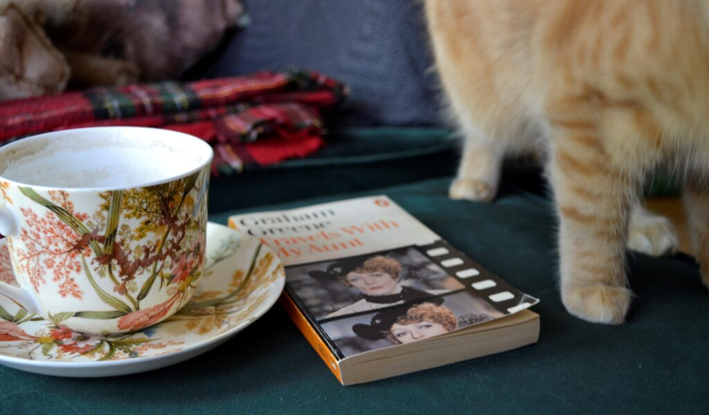 A teacup and orange paws beside Travels with My Aunt.