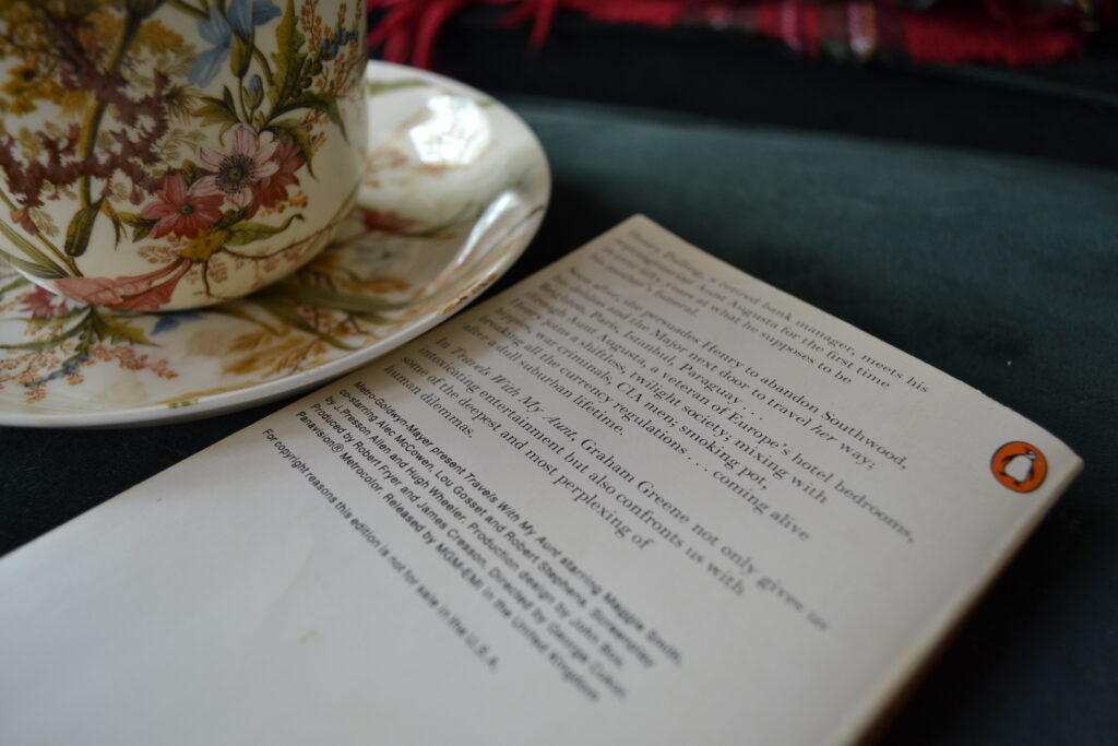 The back cover of Travels with My Aunt beside a teacup.