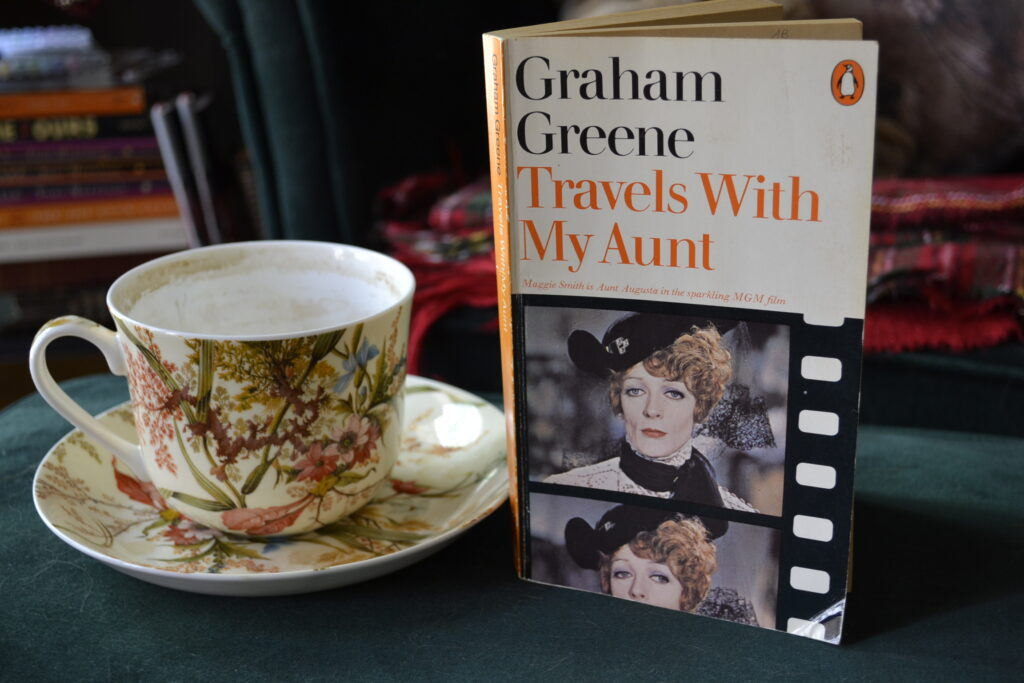 A teacup and the front cover of a vintage penguin edition of Travels with My Aunt.