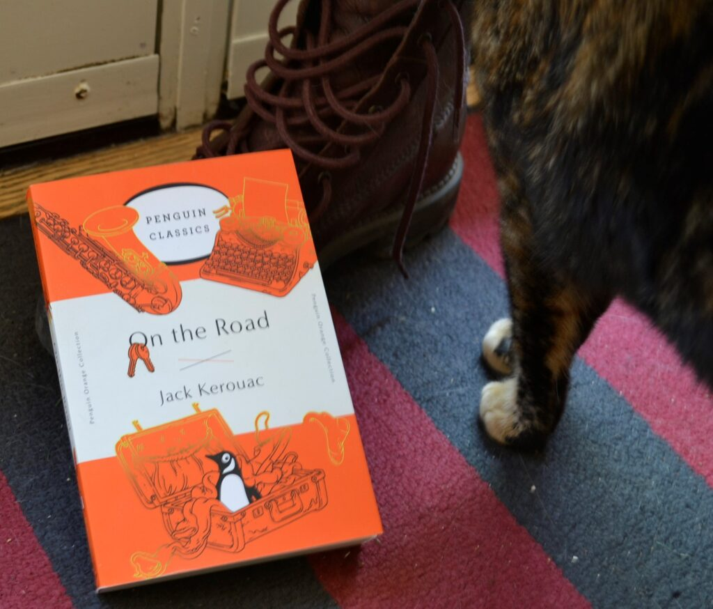 A tortoiseshell cat standing beside an orange copy of On the Road and a brown boot.