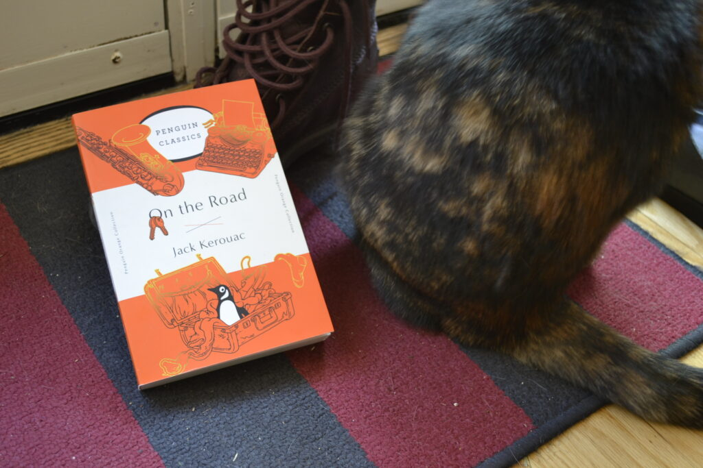 A tortoiseshell cat beside an orange copy of On the Road and a brown boot.
