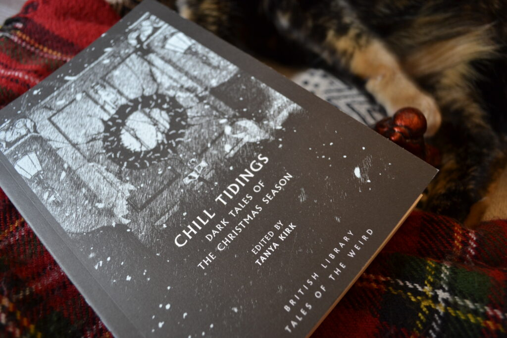 A closeup of the black and white cover of Chill Tidings and a red paw.