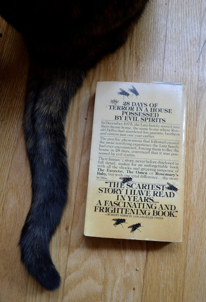 A dark tail flicks beside the back cover, illustrated with flies.