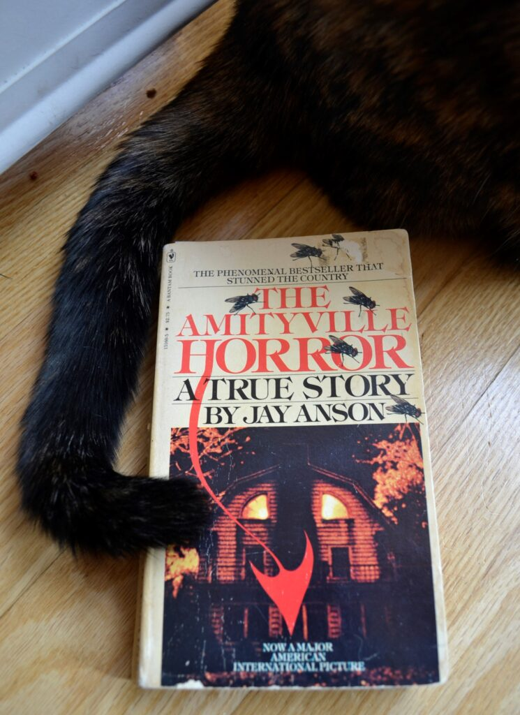 A dark tail curls around the demonic cover of The Amityville Horror.